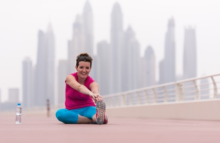 very active young beautiful woman stretching and warming up on the promenade along the ocean side with a big modern city in the background to keep up her fitness levels as much as possible 版權商用圖片