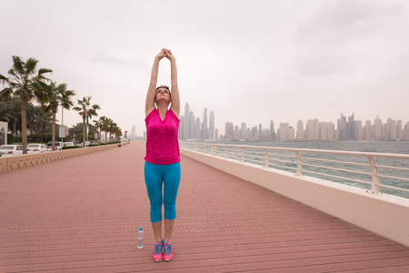 very active young beautiful woman stretching and warming up on the promenade along the ocean side with a big modern city in the background to keep up her fitness levels as much as possible Stock Photo
