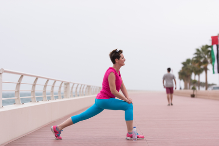 very active young beautiful woman stretching and warming up on the promenade along the ocean side to keep up her fitness levels as much as possible Reklamní fotografie