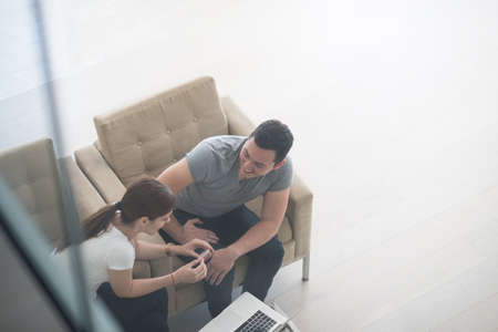 couple on couch: happy young couple buying online using laptop a computer and a credit card in their luxury home villa