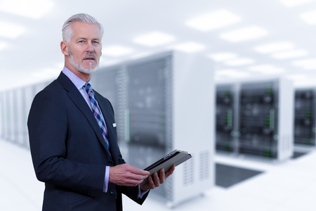 Portrait of senior businessman in big rack server room Stock Photo