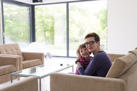 luxury living room: young mother and cute little girl enjoying their free time hugging on the sofa in their luxury home villa Stock Photo