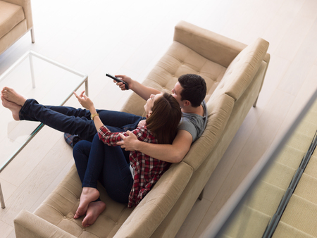 couple on couch: Young couple on the sofa watching television together in their luxury home Stock Photo