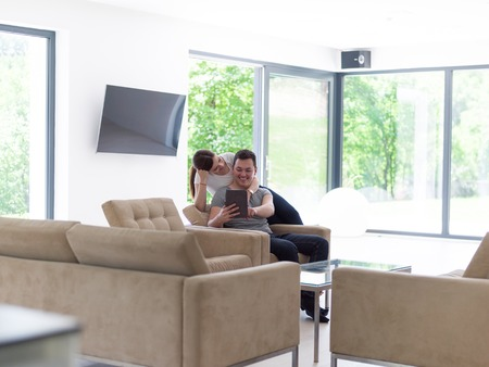 couple on couch: Young couple relaxing at luxurious home with tablet computers reading in the living room on the sofa couch.