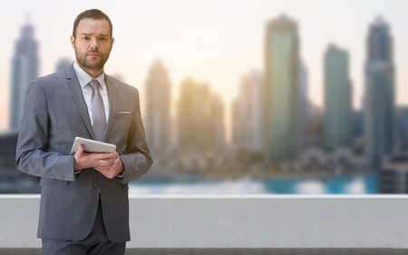 Portrait of young businessman standing on balcony in front of the big city Stock Photo