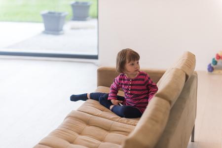 Porträt des netten kleinen Mädchens, das zu Hause Spiele auf Smartphone spielt