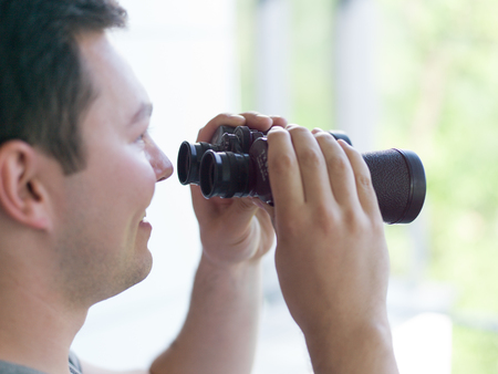 spying: Young man standing looking through a glass window with binoculars as he watches something in the distance