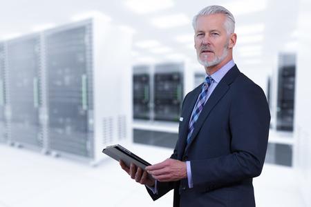Portret van senior zakenman in grote rack server kamer Stockfoto