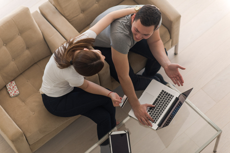 luxury living room: happy young couple buying online using laptop a computer and a credit card in their luxury home villa