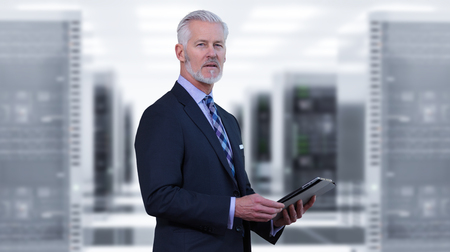 Portrait of senior businessman in big rack server room Stock Photo