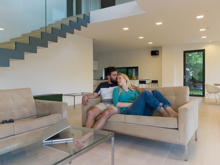 luxury living room: Young couple relaxes on the sofa in the luxury living room, using a laptop and remote control