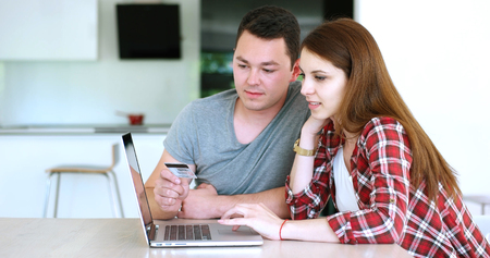 クレジット カードを使ってオンライン購入を行うテーブルに座ってカップル