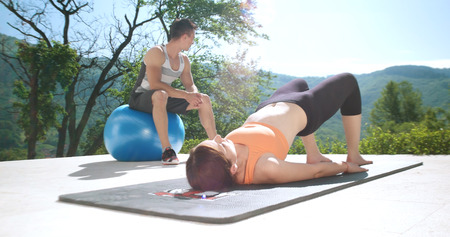 man gym: sporty couple exercising together  on terace in front of mansion