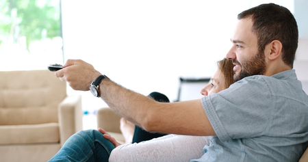 Senior couple sitting in couch and watching tv Stock Photo