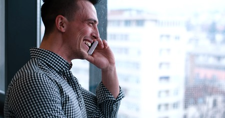 笑い男インテリア オフィスで電話で話しています。 写真素材 - 76532879