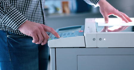 handsom: assistant makes copies of files in the copy machine Stock Photo