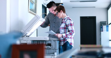 Young Beautiful Woman with assistant Making Copies Of Files In The Copy Machine
