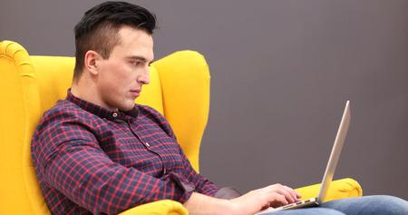 Jeune entrepreneur pigiste travaillant en utilisant un ordinateur portable et espace coworking Banque d'images - 76533300