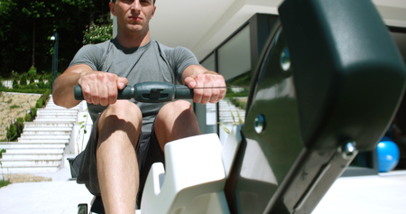 Man Working Out On Row Machine in front of home Stock Photo