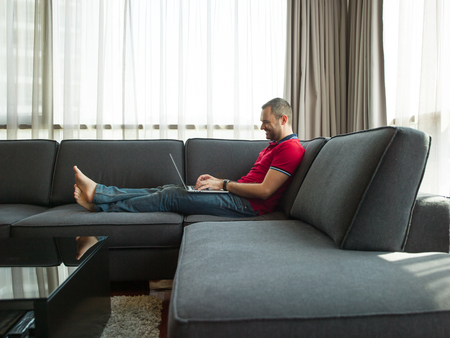 single: Young, handsome man using laptop sitting on sofa