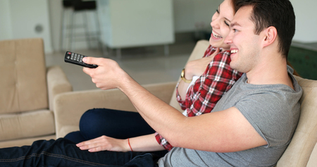 high def: Young couple watching tv in the living roonm