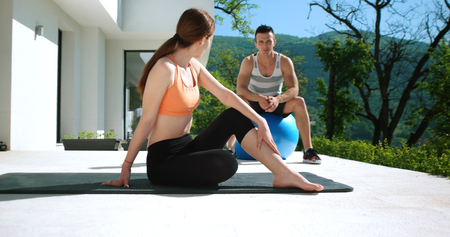sporty couple exercising together  on terace in front of mansion