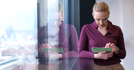 Elegant Woman Using Mobile Phone by window in office building Stock Photo