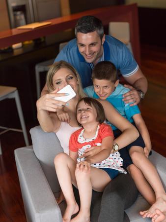 gente sentada: familia feliz emplazamiento en el sofá y el uso de teléfono celular para llamadas de vídeo en casa
