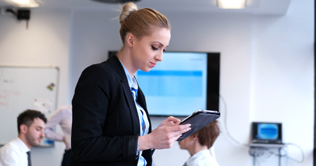 Portrait of  smiling casual businesswoman using tablet  with coworkers standing in background photo