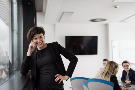 architect: female manager using cell telephone in office interior