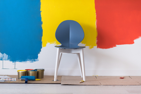 empty chair and equipment for painting in front of colorful wall in the background Stock Photo