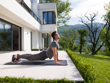 male athlete: young handsome man doing morning yoga exercises in front of his luxury home villa