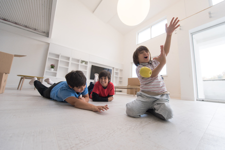 sitting on the ground: happy young boys having fun with an apple on the floor in a new modern home
