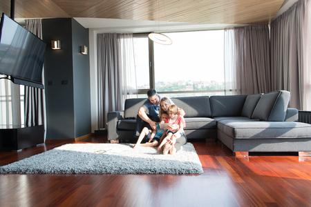 幸せな若い家族再生を一緒にタブレットを家でソファーに座ってください。 写真素材