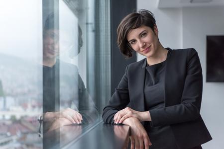 portrait de femme d & # 39 ; affaires prospère par l & # 39 ; escalier de la fenêtre au bureau de travail