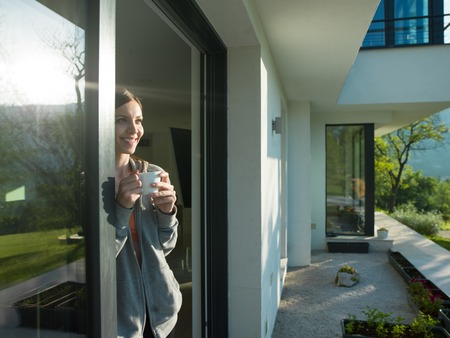 portrait of a young beautiful successful woman drinking coffee in the doorway of her luxury home villa Stock fotó