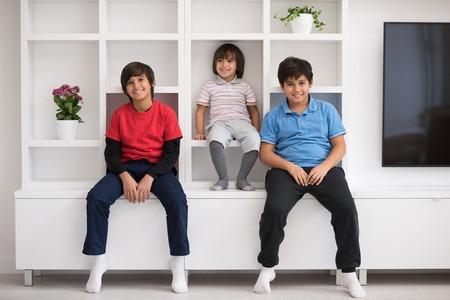 gelukkige jonge jongens hebben plezier terwijl ze op een plank in een nieuw modern huis staan Stockfoto