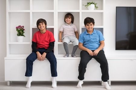 young boys: happy young boys are having fun while posing on a shelf in a new modern home