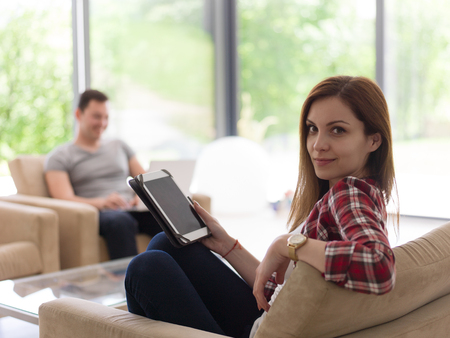 laptop computers: Young couple relaxing at luxurious home with tablet and laptop computers reading in the living room on the sofa couch.