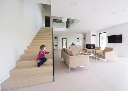 Glückliche junge Familie mit kleinen Mädchen genießt in der modernen Wohnzimmer ihrer Luxus-Villa