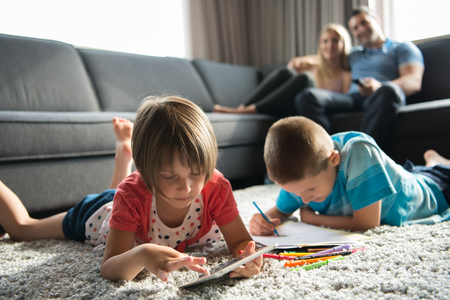 pre: Happy Young Family Playing Together at home on the floor using a tablet and a childrens drawing set Stock Photo
