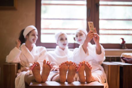 group of famale friends in spa have fun, celebrate bachelorette party with face mask 版權商用圖片 - 78306063