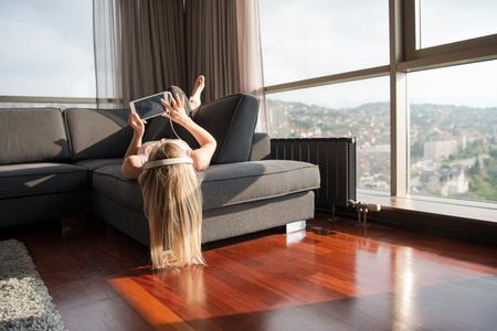 Vrouw luisteren naar muziek met zonlicht uit het venster van het appartement