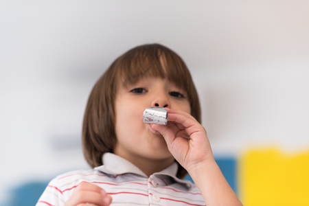 young happy boy having fun and blowing a noisemaker Stock Photo