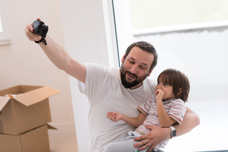young father and his son photographed themselves with cardboard boxes around them while moving into their new home Stok Fotoğraf