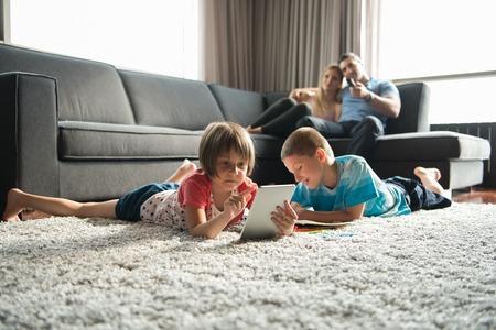 Gelukkige Jonge Familie Spelen Samen thuis op de vloer met behulp van een tablet en een tekenset voor kinderen