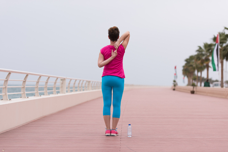 very active young beautiful woman stretching and warming up on the promenade along the ocean side to keep up her fitness levels as much as possible 版權商用圖片