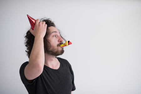 Portrait of a man in party hat blowing in whistle isolated on a white background Stock Photo