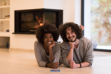 beautiful young multiethnic couple lying on the floor of their luxury home in front of fireplace at autumn day