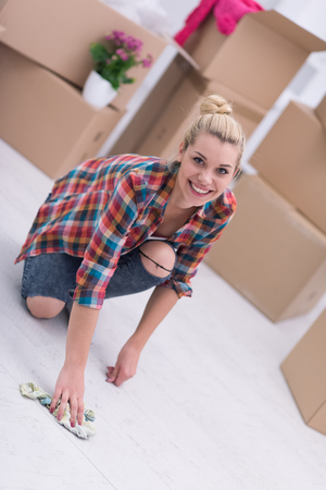 sirviente: young beautiful blonde woman looking at the camera while cleaning the floor at home